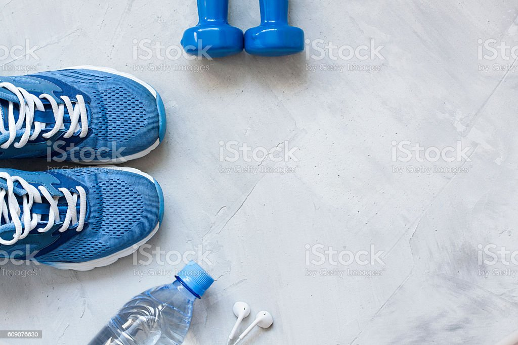 Flat lay sport shoes, bottle of water, dumbbells and earphones stock photo