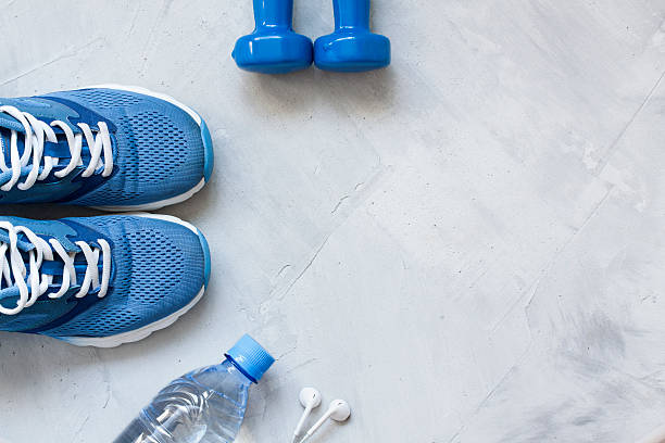 flat lay sport shoes, bottle of water, dumbbells and earphones - スポーツ医学 ストックフォトと画像