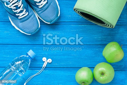 istock Flat lay sport shoes, bottle of water, mat and earphones 609076842