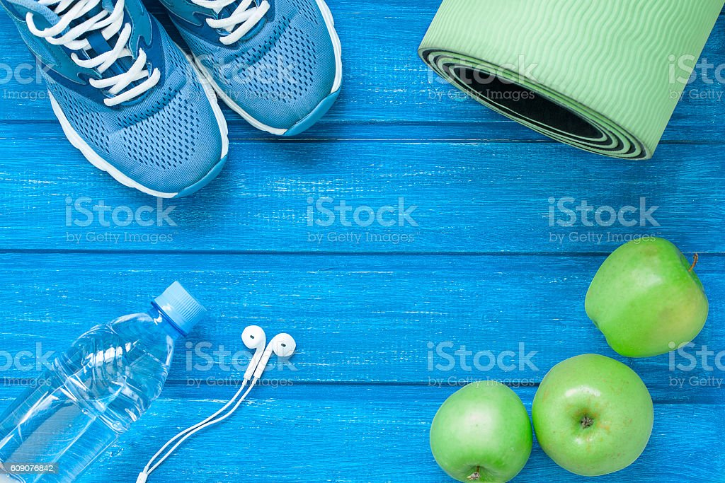 Flat lay sport shoes, bottle of water, mat and earphones stock photo