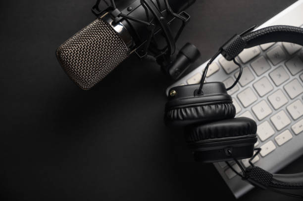 flat lay, studio microfoon met professionele hoofdtelefoon op een pc-toetsenbord. zwart op een zwarte achtergrond. podcasts, radio, streams, bloggen, werken met geluid, het opnemen van tracks - podcast stockfoto's en -beelden