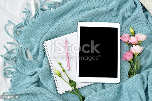 istock Flat lay tablet, phone, cup of coffee and flowers on white blanket with turquoise plaid 840644212