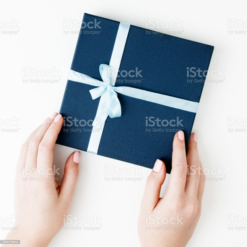 Flat lay. Top view. A minimalistic style of fashion and beauty photography. Hands holding craft paper gift box with as a present for Christmas, new year, valentine day or anniversary stock photo
