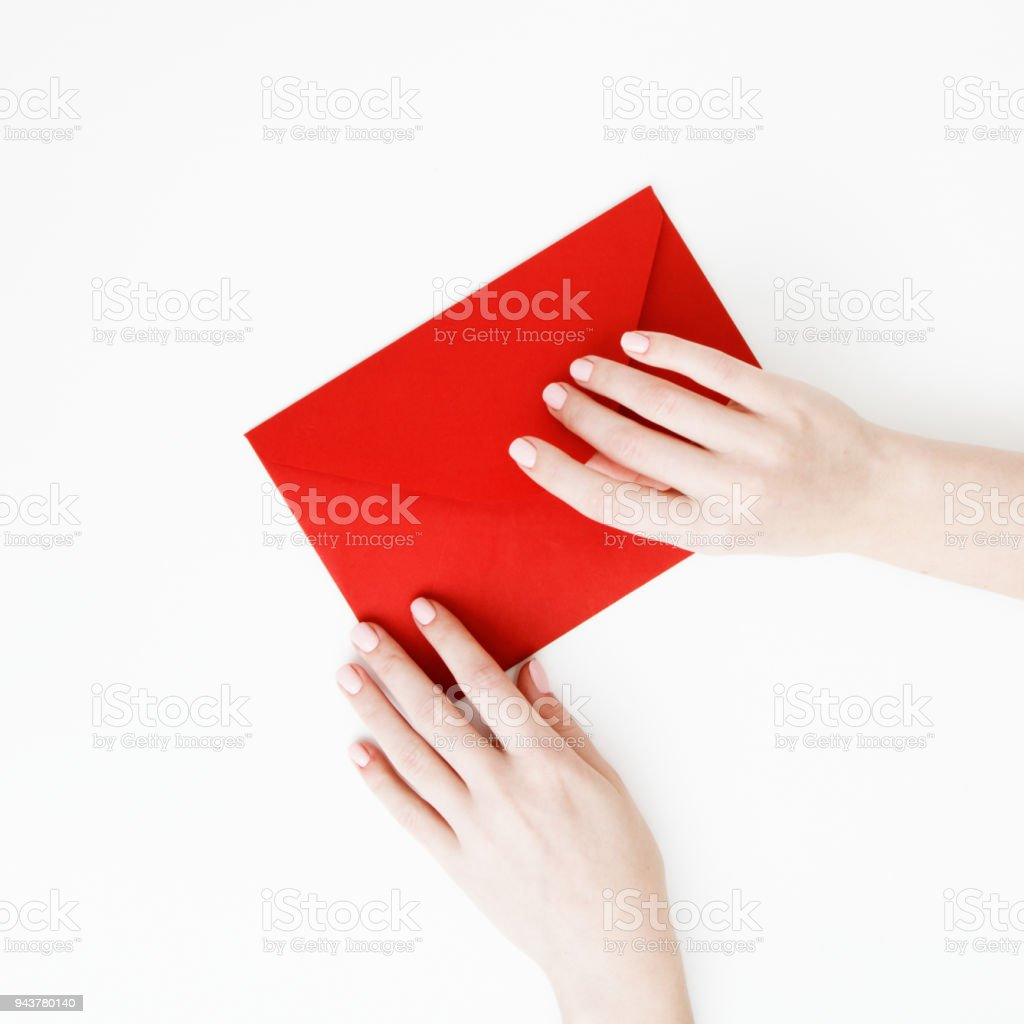 Flat lay. Top view. A minimalistic style of fashion and beauty photography. Hands holding craft paper gift envelope with as a present for Christmas, new year, valentine day or anniversary stock photo