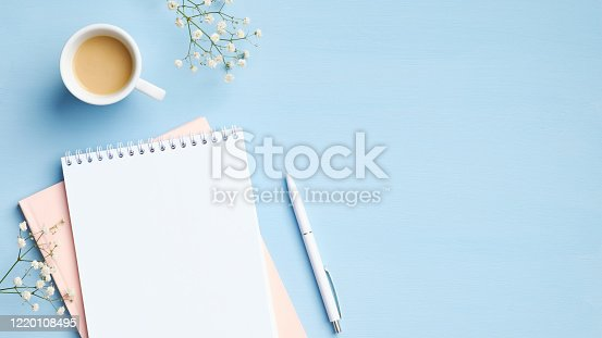 843371502 istock photo Flat lay, top view feminine workspace with blank notepad, cup of coffee, pen and flowers on blue background. Minimal style home office desk, business and education concept 1220108495