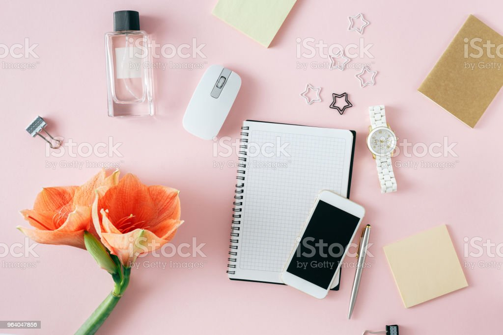 Flat lay, top view office table desk. Feminine desk workspace with flower amaryllis, notebook, pen, smartphone, computer mouse, womens wristwatch and female perfume on pink background - Royalty-free Adult Stock Photo