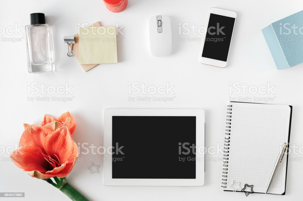 Flat lay, top view office table desk. Feminine desk workspace with flower amaryllis, tablet, notebook with pen, smartphone, computer mouse and female perfume - Royalty-free Adult Stock Photo
