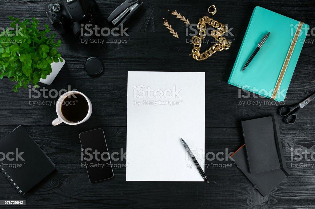 Cadre de vue plate Lapointe, haut bureau table bureau. Espace de travail avec une feuille blanche de papier, Journal de la menthe et appareil mobile sur fond foncé photo libre de droits