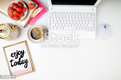 509867718istockphoto Flat lay trendy feminine home workspace. Home office desk with laptop, notebook, fresh strawberries and coffee cup on white background. Flat lay 972569808