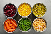 Flat lay view at canned carrots, chickpeas, kidney beans, green beans, peas and corn in opened tin cans on kitchen table. Non-perishable foods background
