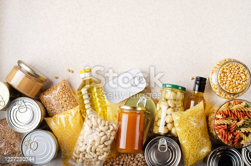 istock Flat lay view at kitchen table full with non-perishable foods. Spase for text 1227210244