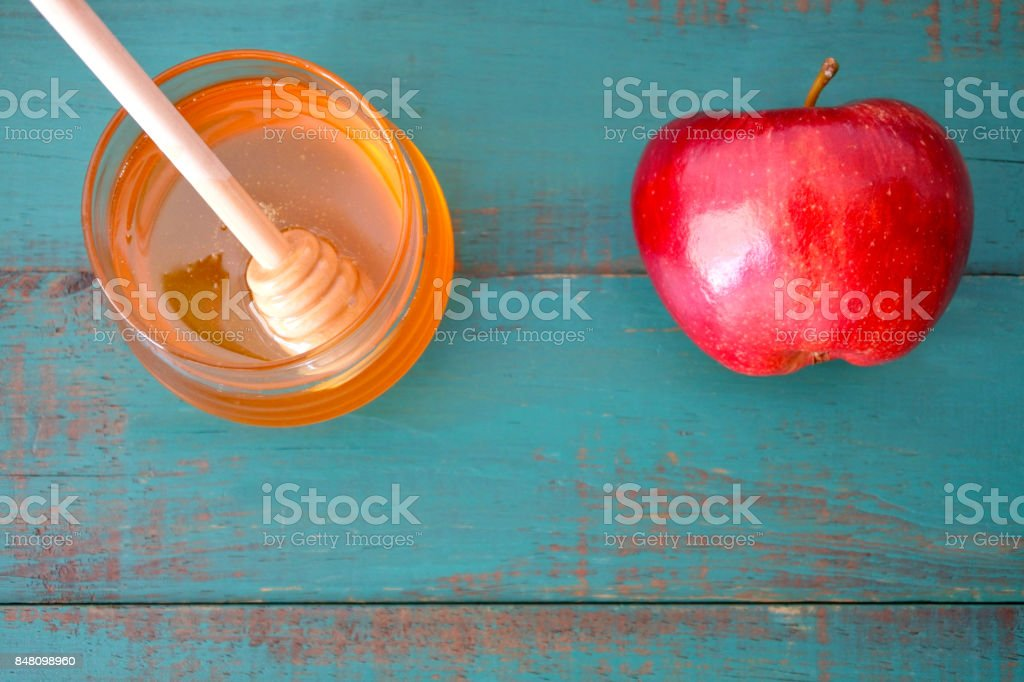 Flat lay view of honey jar and red apple on a turquoise background stock photo