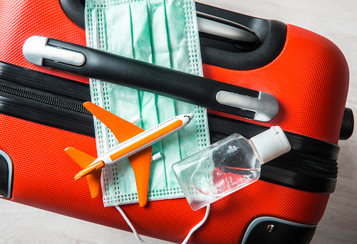Flat lay view of medical face mask with airplane figurine on traveling baggage suitcase with small portable hand sanitizer bottle. Traveling during coronavirus outbreak concept. Year 2020.