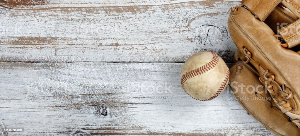 Flat lay view of old baseball and mitt on white rustic wooden boards stock photo
