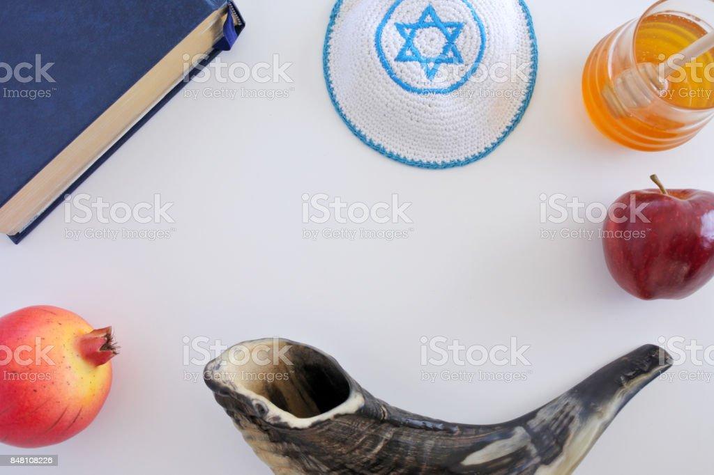 Flat lay view of Shofar, Torah book, Kippa, apple, honey and Pomegranate background stock photo