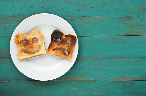 Flat lay view of two slices of toasted bread Flat lay view of two slices of toasted bread in a white plate. One is burned and one is well done. Relationship lifestyle concept. copy space negative emotion stock pictures, royalty-free photos & images