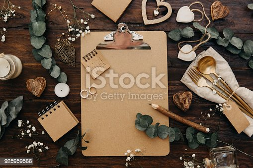 Flat lay Wedding planning. Craft clipboard with rustic decorations on wooden background. Vintage Greenery Wedding Details