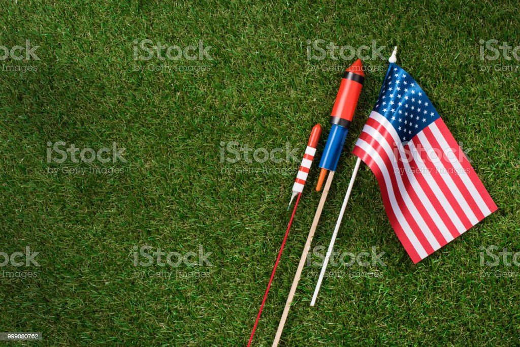 flat lay with american flagpole and fireworks on green grass, americas independence day concept flat lay with american flagpole and fireworks on green grass, americas independence day concept American Culture Stock Photo