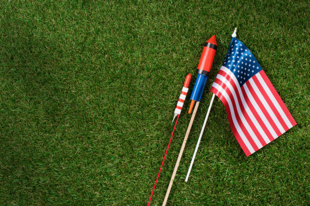 flat lay with american flagpole and fireworks on green grass, americas independence day concept stock photo
