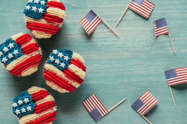 flat lay with arranged cupcakes and american flags on wooden tabletop, presidents day celebration concept - fourth of july zdjęcia i obrazy z banku zdjęć