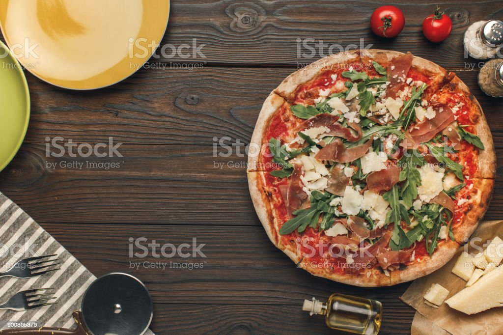 flat lay with arranged italian pizza, cutlery and various ingredients...