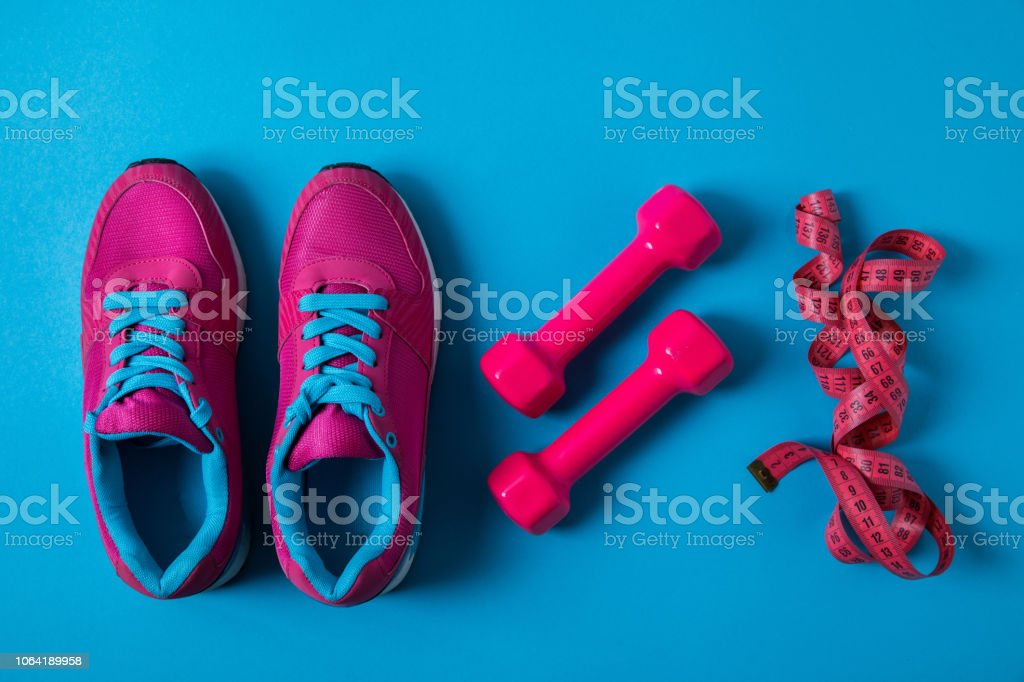 flat lay with arranged pink sneakers, dumbbells and measuring tape...