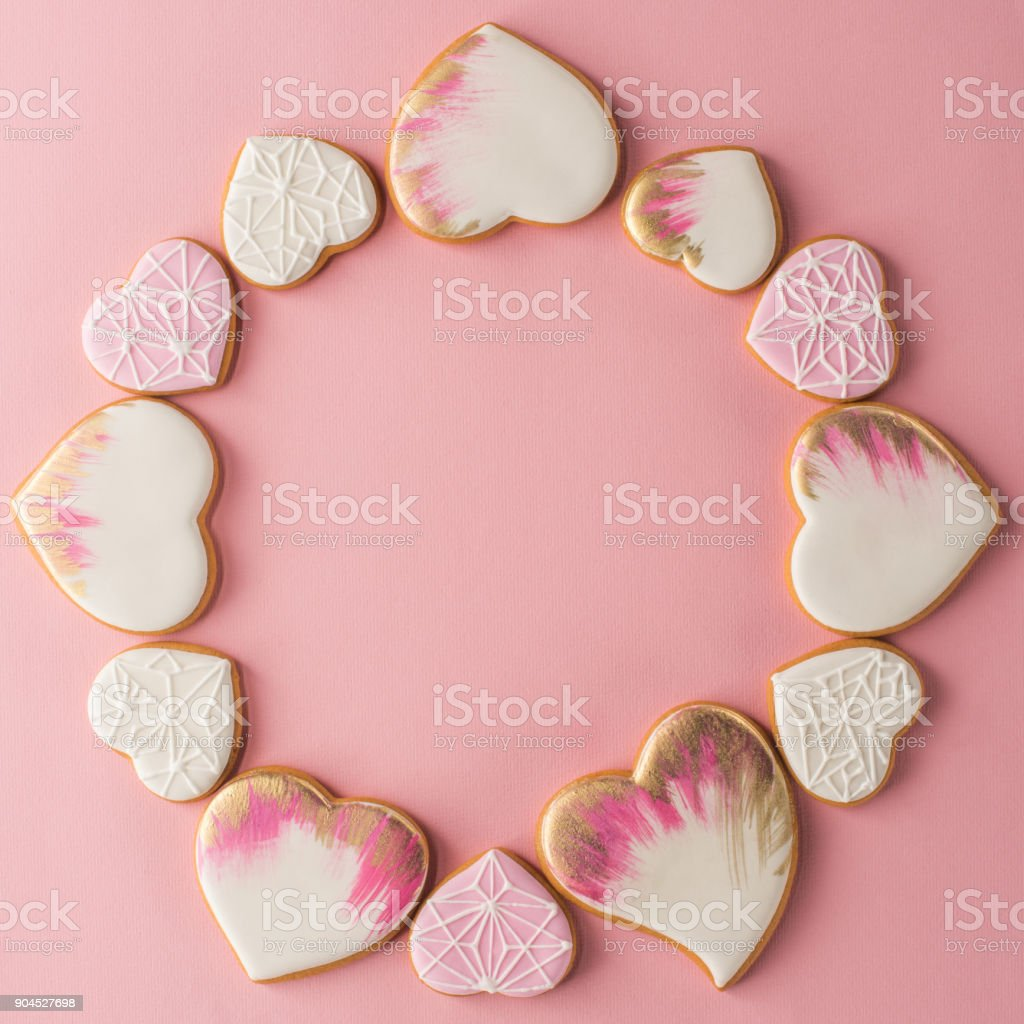flat lay with arrangement of glazed heart shaped cookies isolated on pink surface stock photo