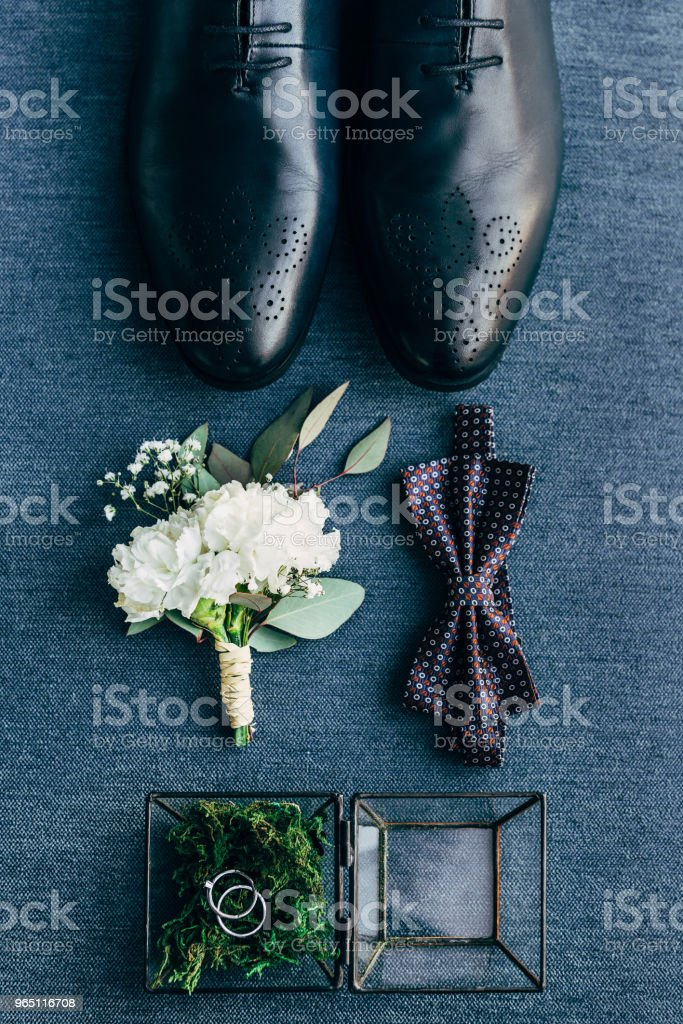 flat lay with arrangement of grooms shoes, bow tie, corsage and wedding rings for rustic wedding on blue background stock photo