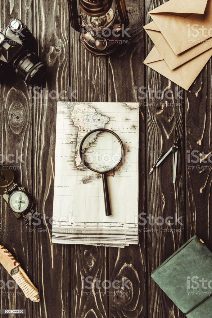 flat lay with arrangement of map, magnifying glass, envelopes, retro photo camera and notebook on dark tabletop - Royalty-free Arrangement Stock Photo