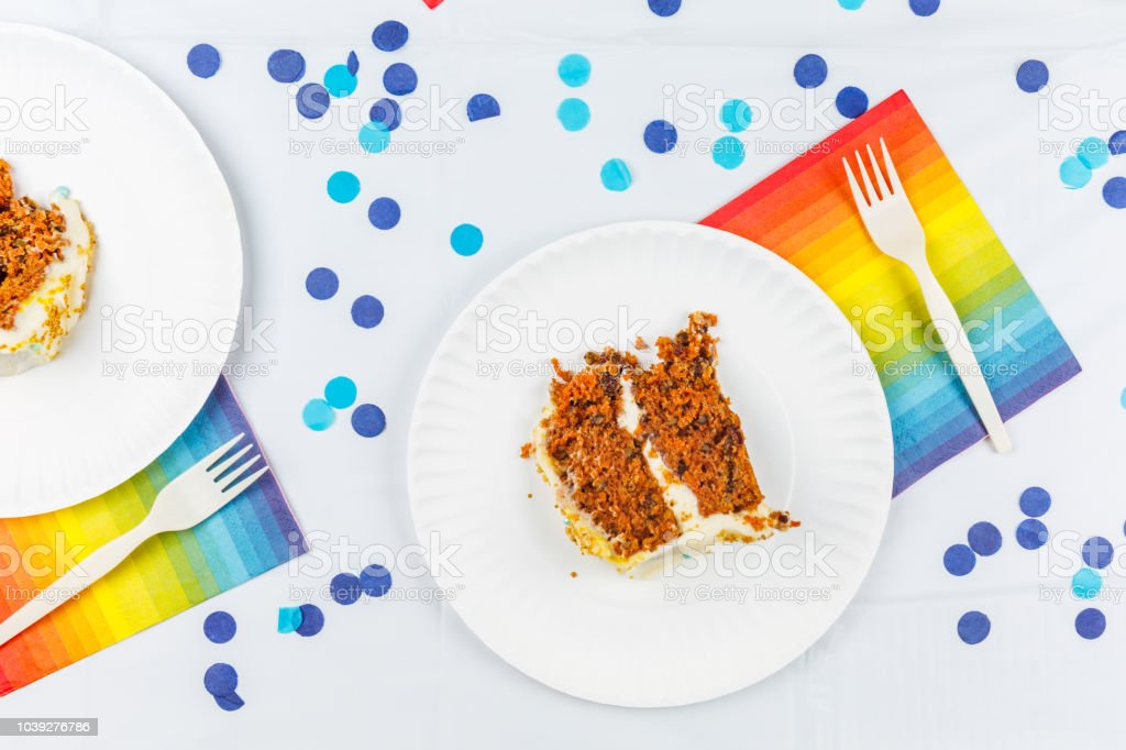 Flat lay with birthday cake pieces on white paper plates. Birthday party celebration concept. stock photo