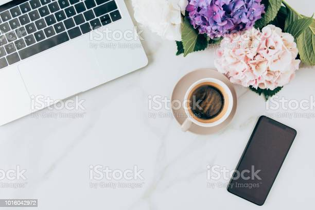 Photo of flat lay with coffee, laptop, smartphone and hortensia flowers on marble surface