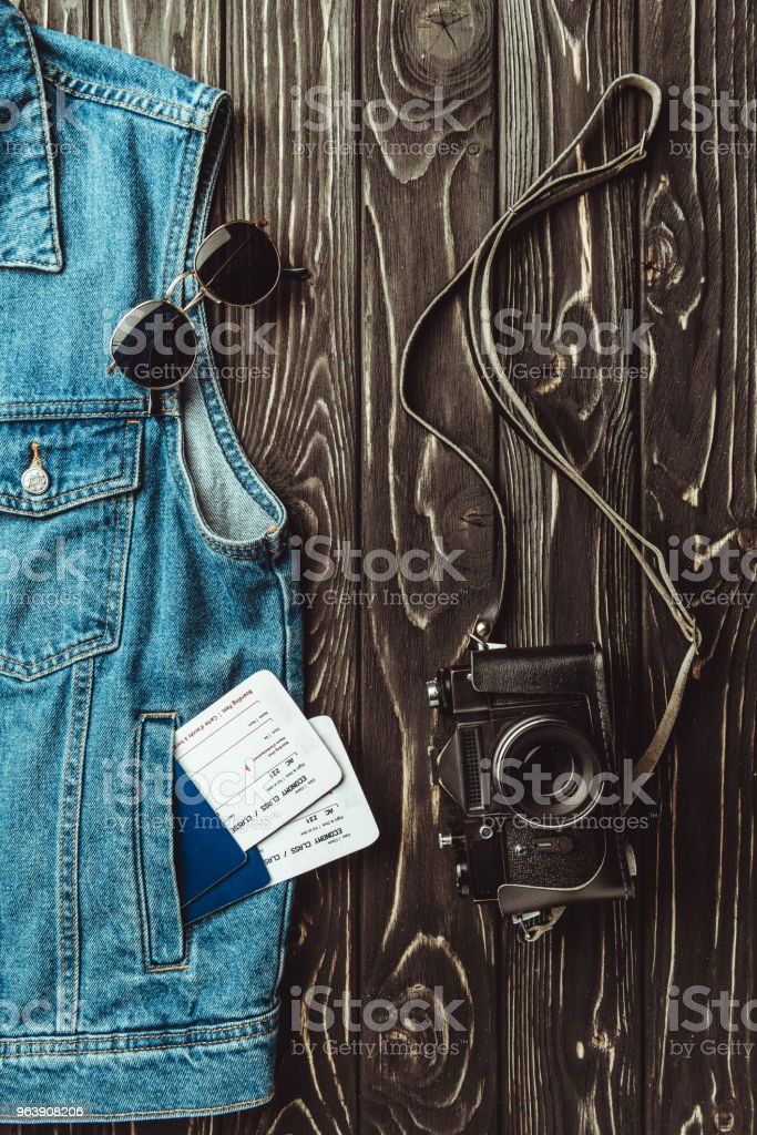 flat lay with denim vest, passports, tickets, sunglasses and retro photo camera on dark wooden surface - Royalty-free Arrangement Stock Photo