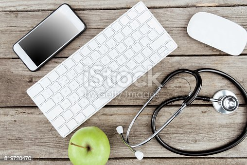 istock flat lay with digital devices, stethoscope and fresh apple on wooden table 819720470
