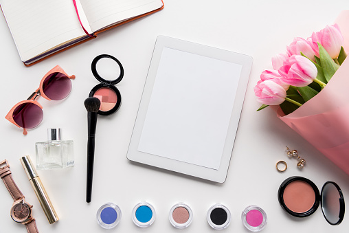 flat lay with digital tablet, various cosmetics, accessories and bouquet of pink tulips