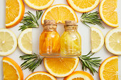 Flat lay with glass bottles and citrus slices with rosemary on white background