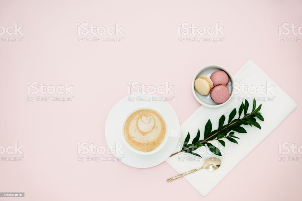Flat lay with green tea latte and maroons over a pink background