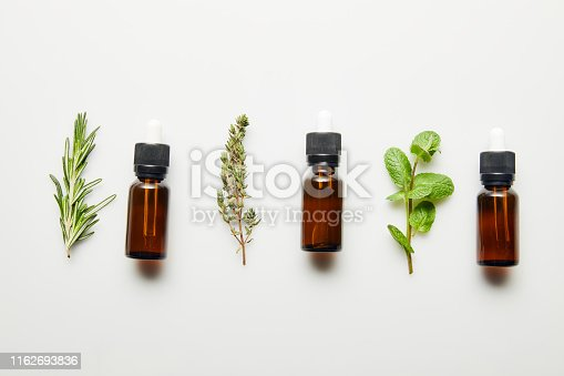 Flat lay with herbs and bottles with essential oil on white background