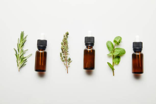 plat lay avec des herbes et des bouteilles avec l'huile essentielle sur le fond blanc - huile photos et images de collection