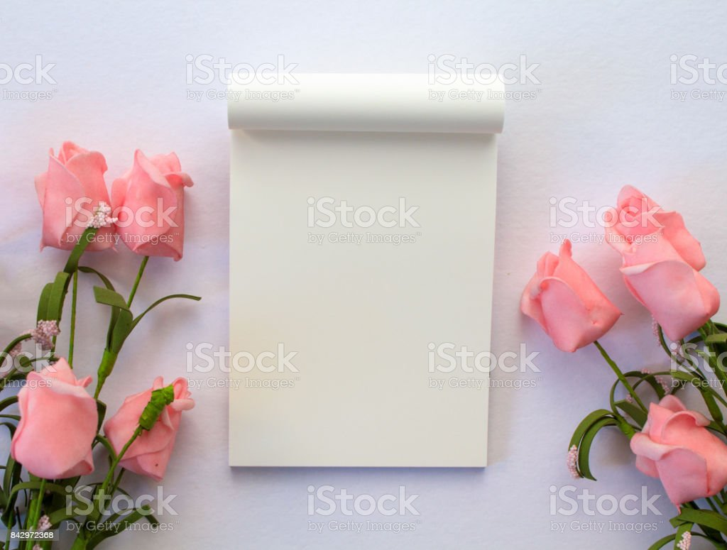Flat lay with notepad and roses on white background. Romantic banner template with text place. stock photo