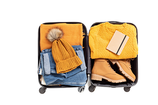 Flat lay with open suitcase with casual clothes for autumn, winter vacations over white background. Winter holidays, travel, tourism, flight luggage concept. Top view