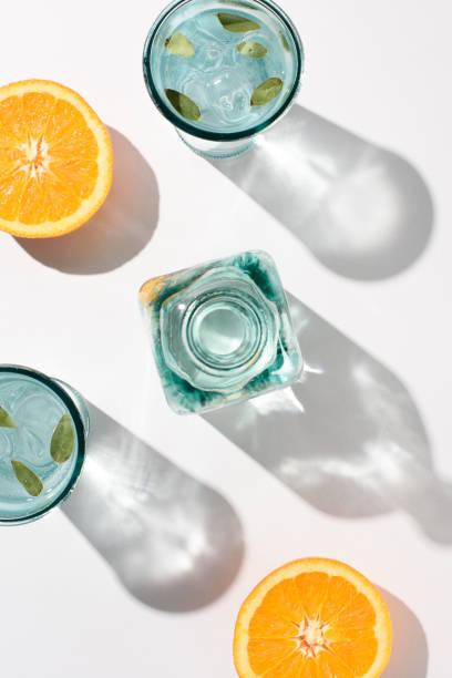 オレンジ、ボトル、グラス水と白い表面に氷の部分とフラット レイアウト - グラス ストックフォトと画像