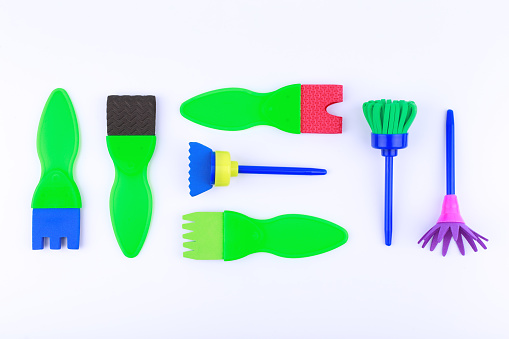 Flat lay with set of brushes for painting isolated on white background. Variation of bright green brushes for artist. Top view, flat lay, white background