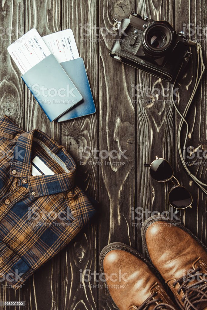 flat lay with shirt, shoes, passports with tickets, sunglasses and retro photo camera on dark wooden surface - Royalty-free Arrangement Stock Photo
