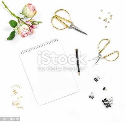 Flat lay with sketchbook, flowers, office tools on white background