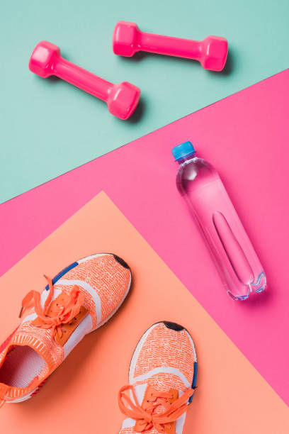 flat lay with sneakers, dumbbells and sport bottle on colorful background - тренажер стоковые фото и изображения