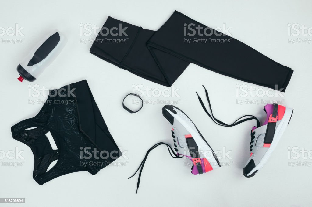 flat lay with sportswear with sneakers, fitness tracker and sports bottle isolated on grey - foto stock