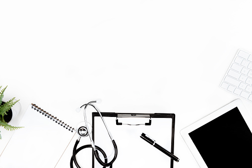 flat lay with stethoscope, clipboard, empty notebook and digital devices isolated on white