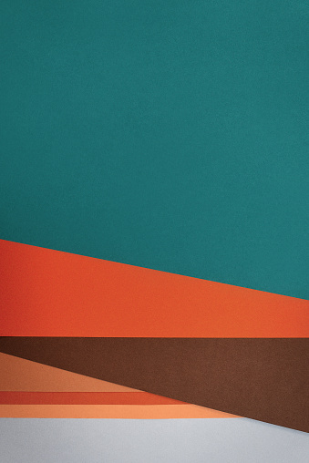 Flat lay with textured papers in vintage shades such as blue-green, orange and ochre