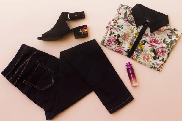 plat lag vrouw kleding en accessoires collage met zomers bloem borduurwerk sandaal, zwarte jeans, floral shirt, parfum - zwarte spijkerbroek stockfoto's en -beelden