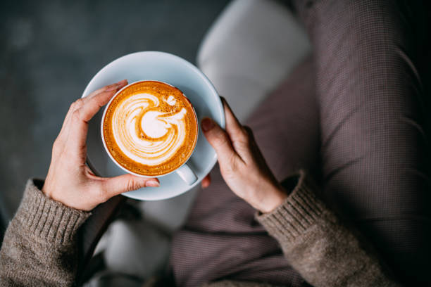 flat lay woman hand holding coffee latte - coffee imagens e fotografias de stock